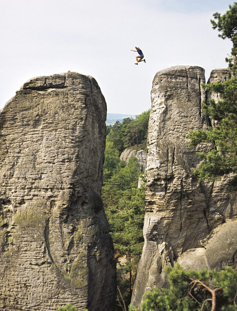 """Karel Vlček fotil pískovcové lezce a skokany od šedesátých let do sametové revoluce. """"Byl jsem velký manipulátor, a když jsem něco chtěl, tak jsem toho dosáh,"""" když byl přeskok lehčí, nutil lezce skákat tam a zpátky. Na fotografii Petr Prachtel v Prachovských skalách skáče z Kobylí věže na Kobylu v Laholském údolí. Fotografováno Praktisixem 6x6 cm."""